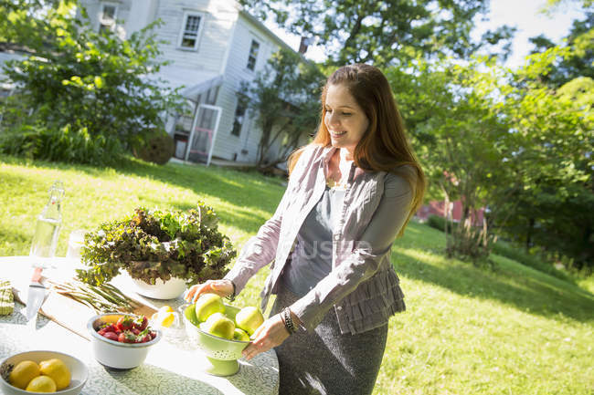 Woman in farmhouse garden preparing table with fresh organic vegetables and fruits. — Stock Photo