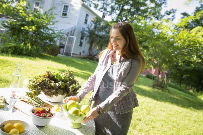 Mulher na mesa de preparação quinta jardim com frutas e legumes orgânicos frescos. — Fotografia de Stock