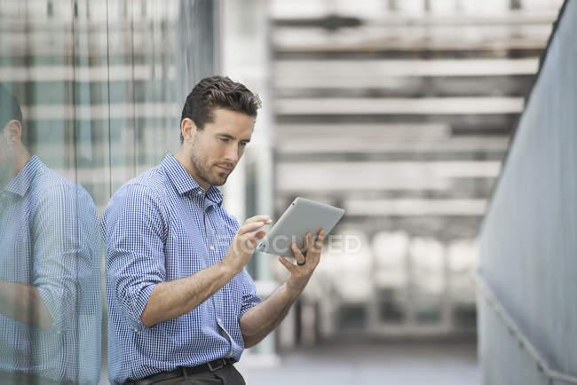 Молодой человек стоит снаружи здания со стеклянными наружными панелями и с помощью цифрового планшета . — стоковое фото