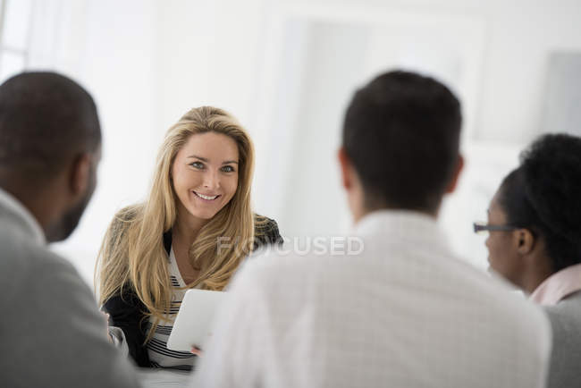 Small group of men and women sitting around table at business meeting in office. — Stock Photo