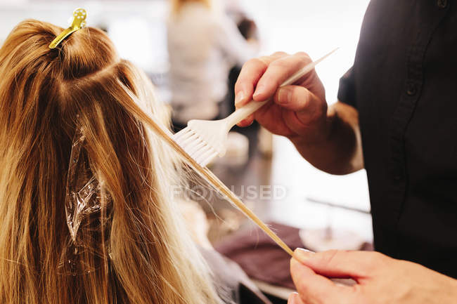 Male hairstylist using paintbrush for dyeing female blonde hair. — Stock Photo