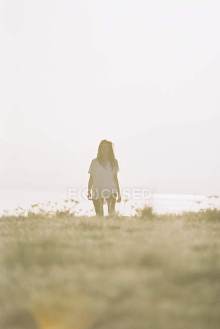Woman with long hair wearing white shirt standing on grass slope. — Stock Photo