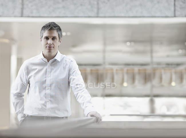 Людина в білій сорочці з відкритим коміром в просторі будівлі, спершись на перила. — стокове фото