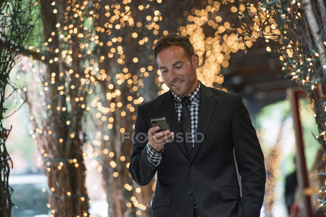 Man checking phone while walking under pergola lit with fairy lights. — Stock Photo