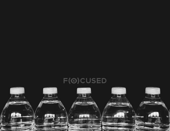 Fila de garrafas de água de plástico transparente cheias de água filtrada sobre fundo preto . — Fotografia de Stock