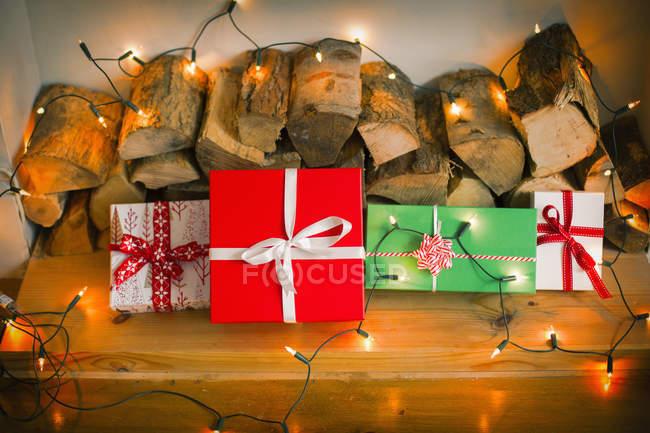 Scatole regalo legate con nastri e luci fatate su tronchi, nature morte . — Foto stock