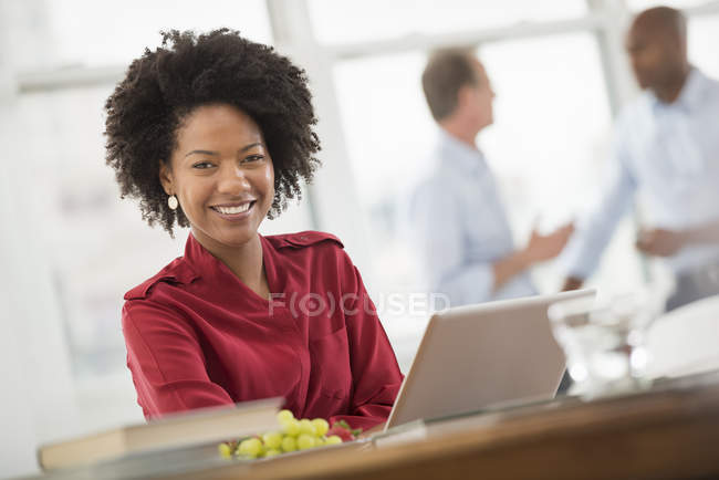 Mid adult woman sitting at desk and using laptop in office with coworkers in background. — Stock Photo