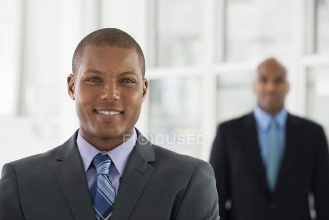 Двое мужчин в костюмах, стоя в офисе и глядя в камеру. — стоковое фото