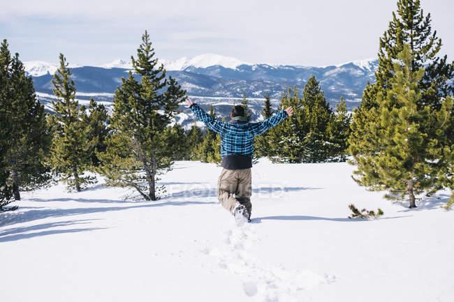 Rear view of man running through deep snow on mountainside. — Stock Photo