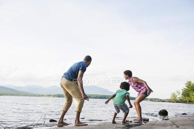 Familie mit Sohn am Ufer des Sees im Wald spielen — Stockfoto