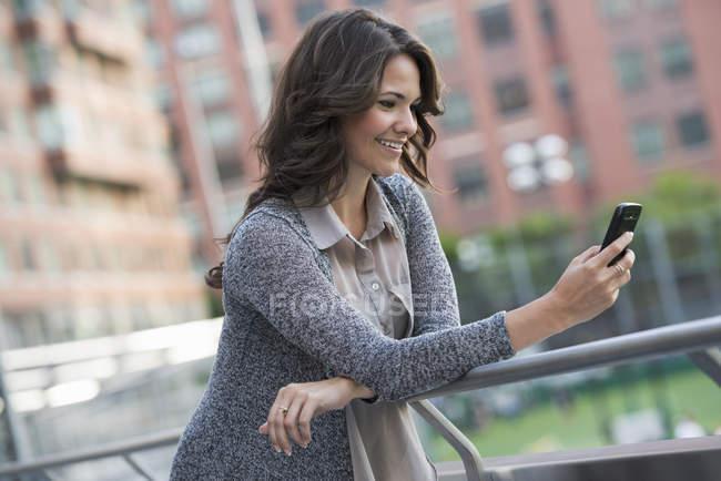 Молодая деловая женщина в сером кардигане с помощью смартфона на улице . — стоковое фото