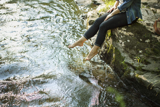 Woman sitting at water edge and paddling feet in stream. — Stock Photo