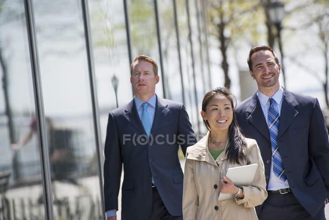 Femme d'affaires et hommes d'affaires marchant ensemble dans la rue de la ville . — Photo de stock
