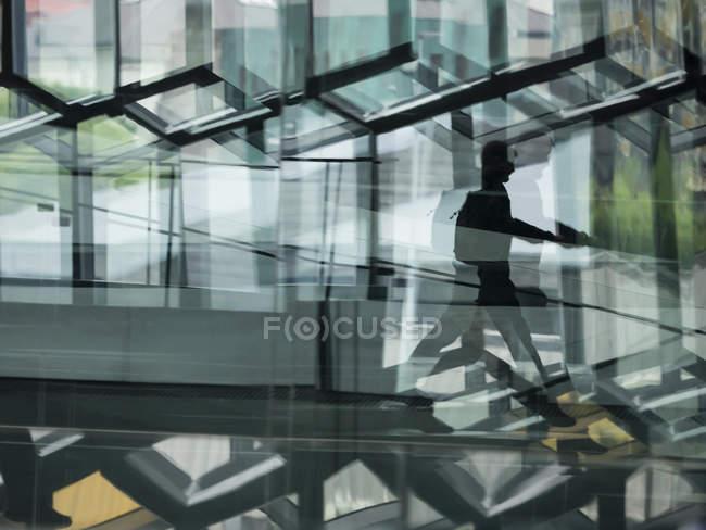 Hombre caminando a través de la construcción con pared de cristal que reflejan la luz - foto de stock