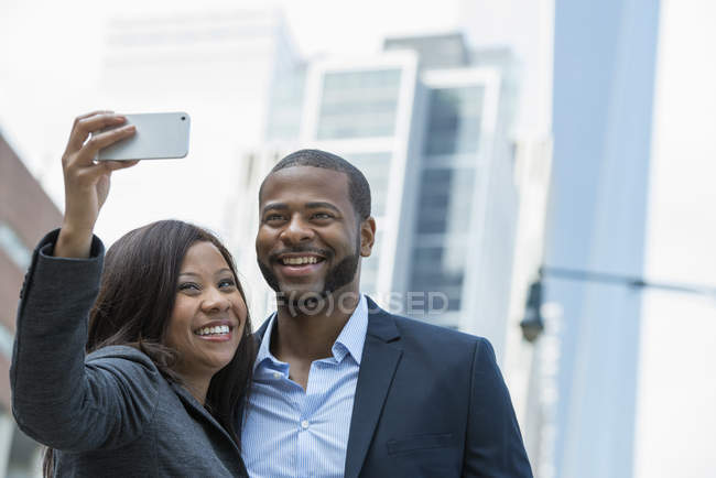 Businessman and businesswoman taking selfie in city downtown. — Stock Photo