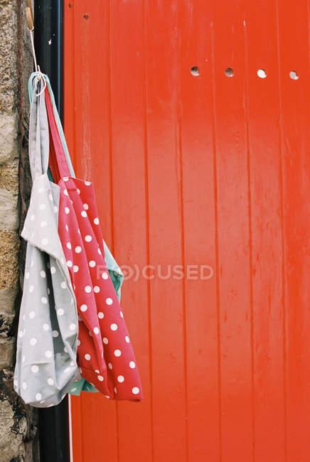Vividamente dipinto porta arancione e borse di stoffa macchiato appeso al chiodo . — Foto stock