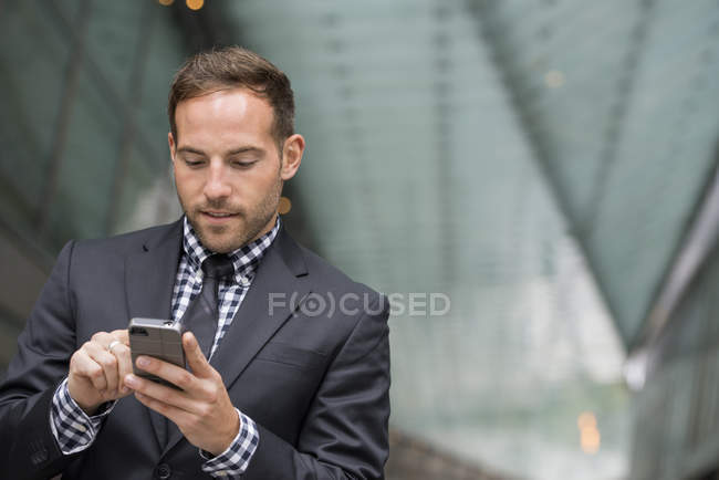 Man with short red hair and beard in suit using smartphone in street. — Stock Photo