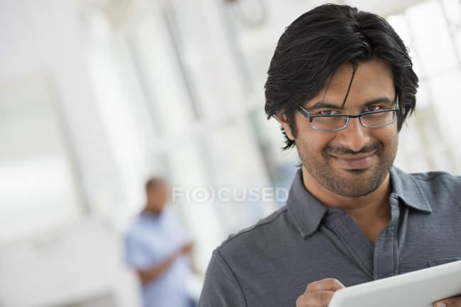 Uomo maturo in possesso di tablet digitale e guardando nella fotocamera in ufficio . — Foto stock