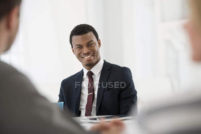 Junger Geschäftsmann im Anzug mit Tasse Kaffee mit digital-Tablette auf Tabelle mit Treffen mit paar — Stockfoto
