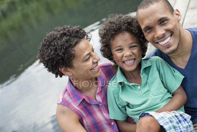 Portrait of happy parents and elementary age boy by lake in summer. — Stock Photo