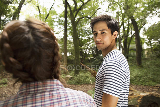 Mixed race man looking over shoulder with young woman in forest. — Stock Photo
