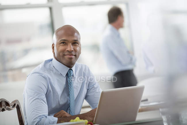 Mid adult man sitting at desk and using laptop in office workplace. — Stock Photo