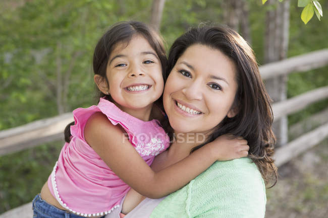 Mother in park posing with daughter, smiling and looking in camera. — Stock Photo