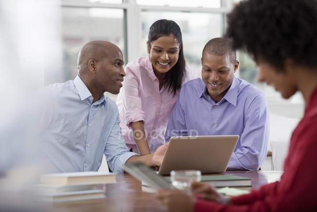 Колеги працюють навколо столу і використанням цифрових планшетів і ноутбук. — стокове фото