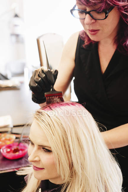 Female hair colorist in gloves applying red hair dye to client blonde hair with brush. — Stock Photo