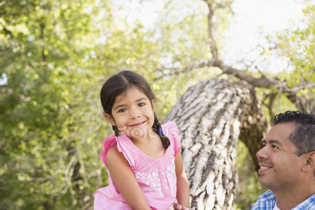 Elementary age girl sitting on tree trunk beside father and looking in camera. — Stock Photo