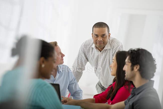 Мужчина, прислонившийся к столу и смотрящий в камеру на встречу с коллегами в офисе . — стоковое фото
