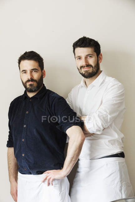 Half-length portrait of two bearded men in white aprons looking in camera. — Stock Photo