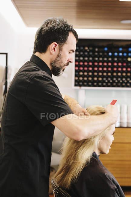 Maturo parrucchiere maschile che lavora sui capelli del cliente e applica la tintura per capelli nel salone . — Foto stock