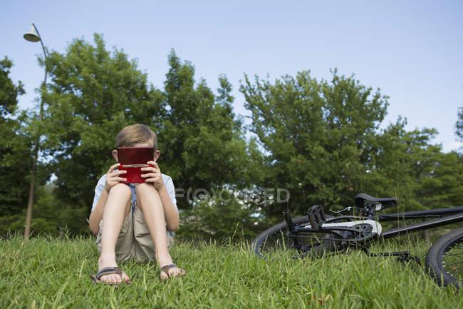 Menino da idade elementar sentado na grama de bicicleta e jogando jogo eletrônico portátil . — Fotografia de Stock