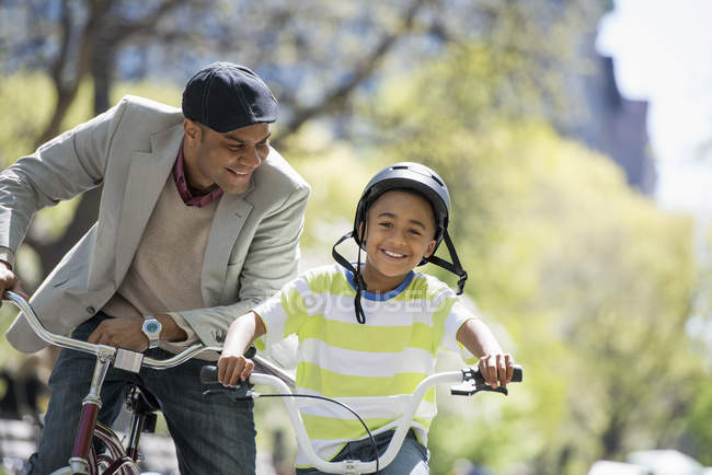 Father and son cycling on bicycles side by side in sunny park. — Stock Photo