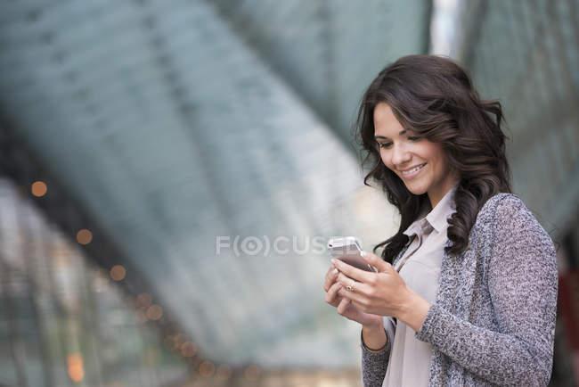 Молодий підприємець у сірий Жакет, посміхаючись і за допомогою смартфона. — стокове фото