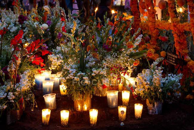Decorazioni di fiori e candele sul cimitero durante la giornata di celebrazione guasto — Foto stock