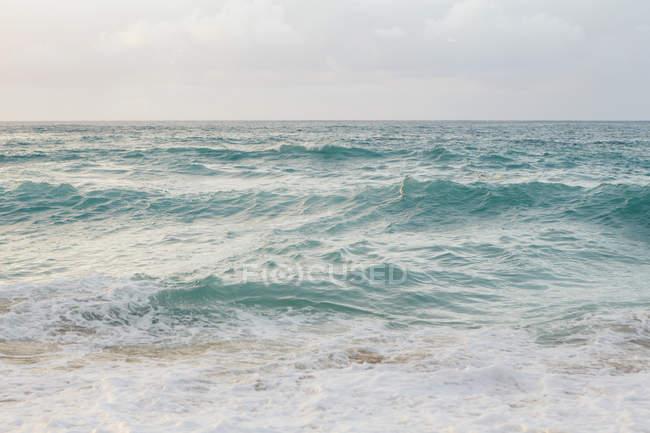 Océan Pacifique vagues de surf au crépuscule à Hawaï littoral . — Photo de stock