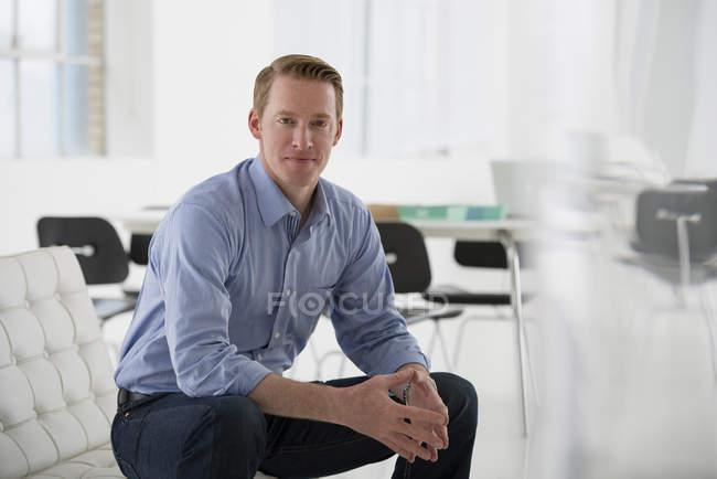 Uomo in camicia blu seduto con le mani strette in posa rilassata e sicura in ufficio . — Foto stock