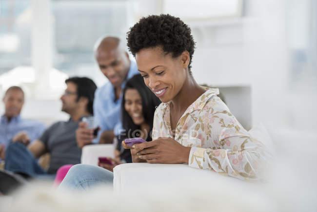 Femme adulte moyenne vérifiant smartphone avec des personnes faisant la fête en arrière-plan . — Photo de stock