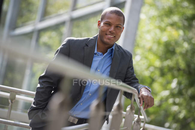 Young businessman in jacket leaning on railing in city. — Stock Photo
