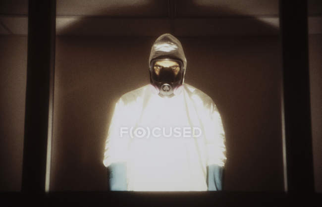 Man in hazardous material protective clean suit standing behind window with illumination. — Stock Photo