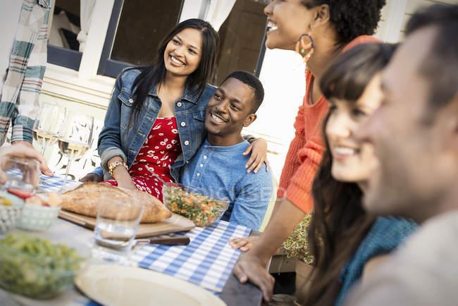 Couple gai avec des amis autour de la table à manger — Photo de stock