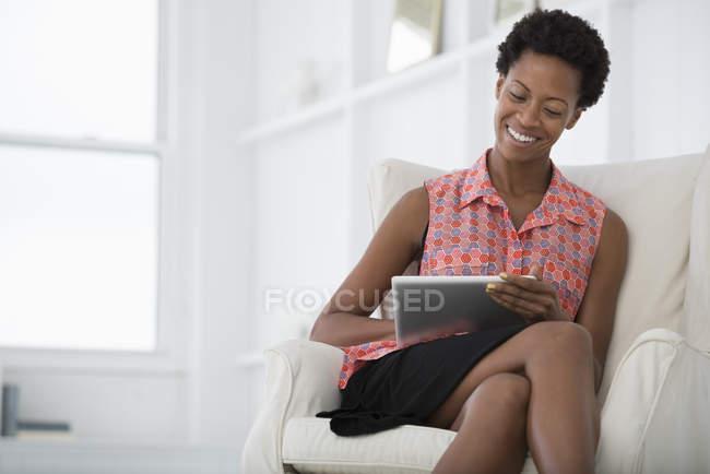 Mitte erwachsene Frau sitzt auf weißem Sofa und nutzt digitales Tablet. — Stockfoto