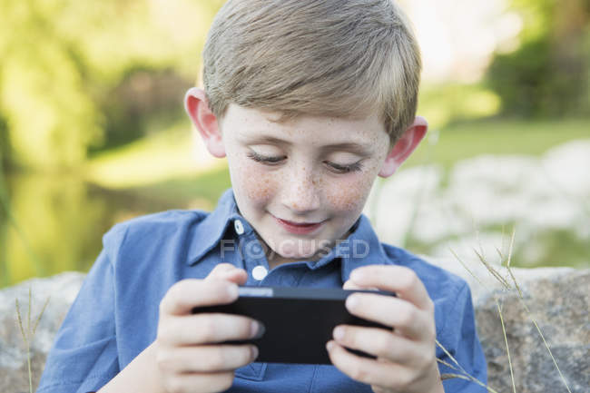 Elementary age boy outdoors leaning against rock and using handheld electronic game. — Stock Photo