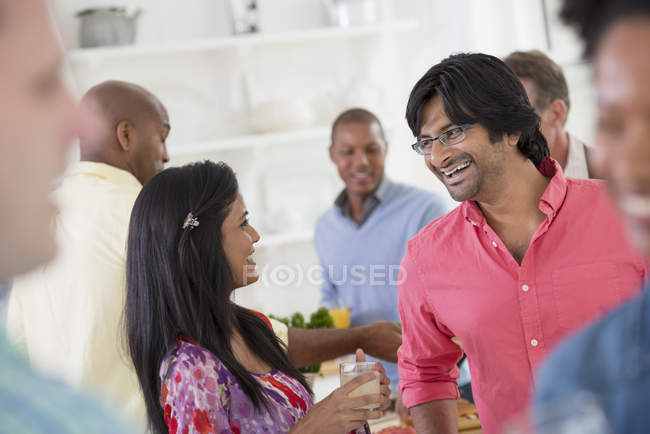Man and woman at center of group of friends at indoor party. — Stock Photo