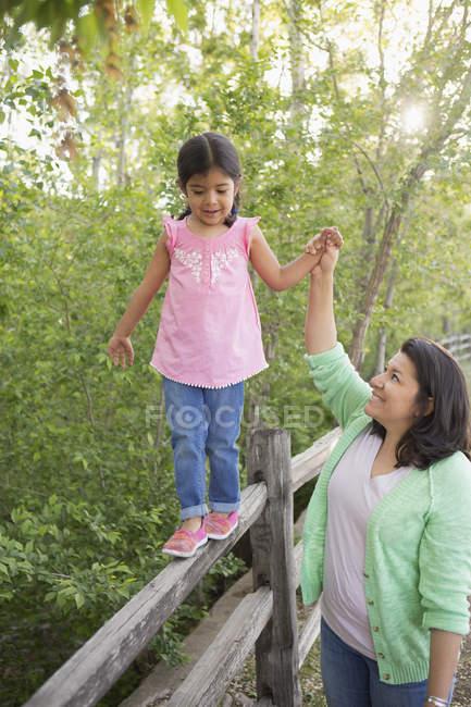 Fille d'âge élémentaire en chemise rose marchant le long de la clôture et tenant la main avec la mère . — Photo de stock