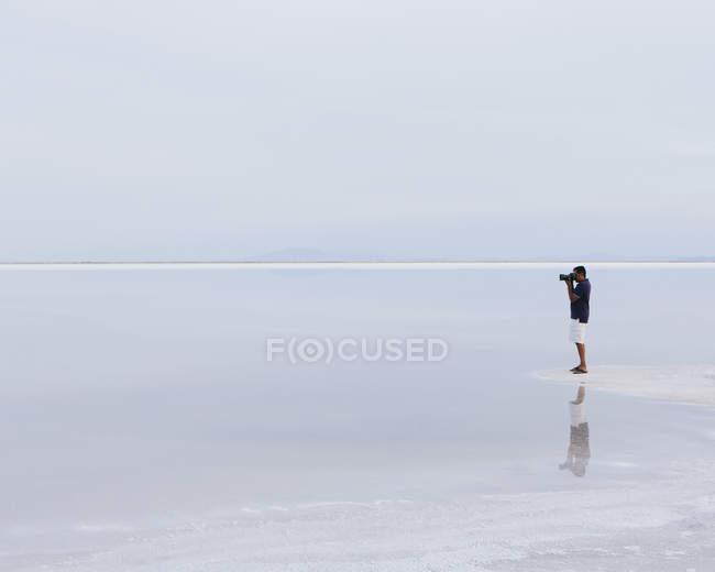 Mann steht am Rand des überfluteten Salzsee von Bonneville und Aufnahme bei Dämmerung, Utah, Usa. — Stockfoto