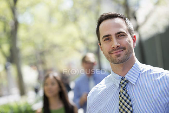 Mid adult man smiling and looking in camera with couple in background. — Stock Photo