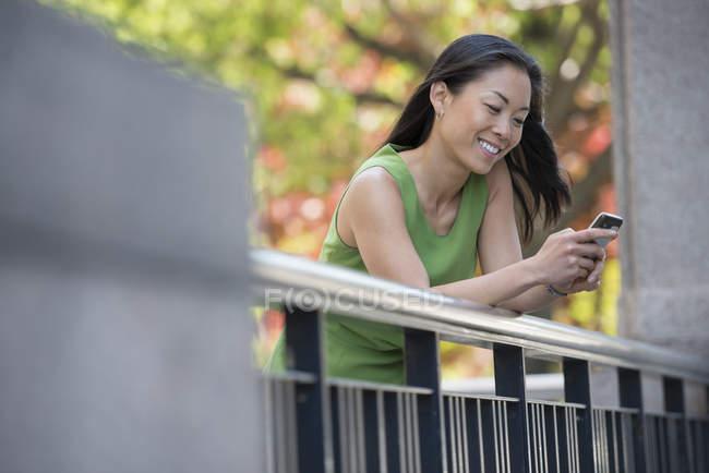 Mulher de vestido verde usando smartphone ao ar livre no parque da cidade sob árvores em flor. — Fotografia de Stock